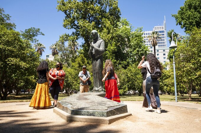 In this June 16, 2020, photo, people gather near the Father Junipero Serra statue on the Capitol Park grounds in Sacramento, Calif. More than a year after protesters toppled the statue of the Spanish missionary on the grounds of the California Capitol, Gov. Gavin Newsom signed a law on Friday, Sept. 24, 2021, to replace it with a memorial for the state's Native people. The statue of Father Junipero Serra had stood in Capitol Park since 1967. (Xavier Mascarenas/The Sacramento Bee via AP, File)