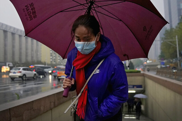 A woman wearing a face mask to help curb the spread of the coronavirus holds an umbrella as she walks out of an underpass tunnel on a rainy morning rush hour in Beijing, Wednesday, Nov. 18, 2020. (AP Photo/Andy Wong)