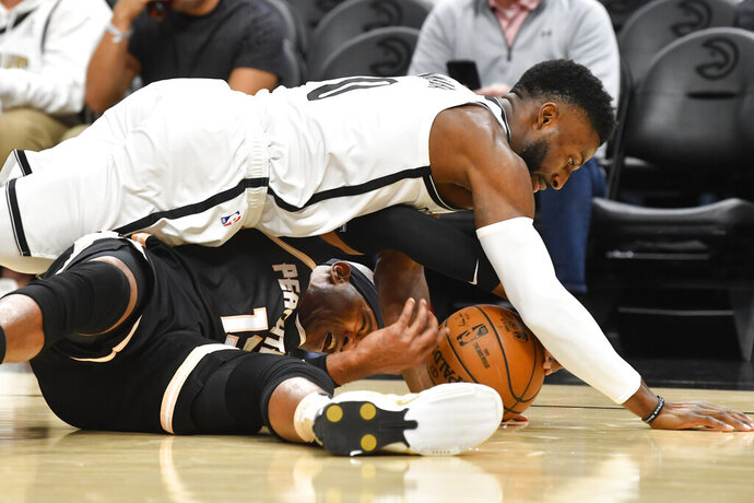 Brooklyn Nets guard David Nwaba, top, and Atlanta Hawks guard Vince Carter vie for a loose ball during the first half of an NBA basketball game Wednesday, Dec. 4, 2019, in Atlanta. (AP Photo/John Amis)