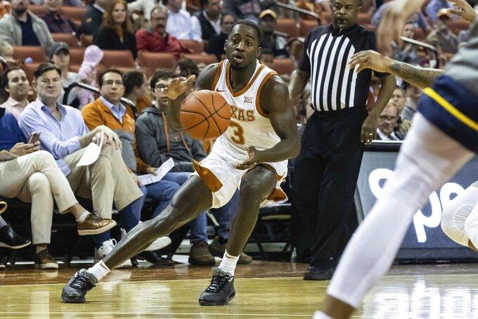 Texas' Courtney Ramey (3) controls the ball during an NCAA college basketball game against West Virginia in Austin, Texas, Monday, Feb. 24, 2020. (Lola Gomez/Austin American-Statesman via AP)