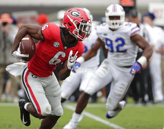 Georgia running back James Cook (6) gains yardage as he is pressured by Florida defensive lineman Jabari Zuniga (92) during the first half of an NCAA college football game Saturday, Oct. 27, 2018, in Jacksonville, Fla. (AP Photo/John Raoux)