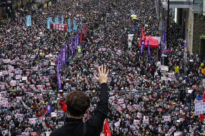 in this Jan. 1, 2020, photo, a protester shows a five demands gesture as Hong Kong people participate in their annual pro-democracy march to insist their five demands be matched by the government in Hong Kong. The city's often-tumultuous street protests had already slowed in the past two months. Now they have ground to an almost complete halt as attention focuses on how to avoid a recurrence of the SARS pandemic, which killed about 300 people in Hong Kong in 2002-03.(AP Photo/Vincent Yu)