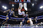Philadelphia 76ers' Ben Simmons (25) hangs from the rim after a dunk past New Orleans Pelicans' Nickeil Alexander-Walker (0) and Jahlil Okafor (8) during the first half of an NBA basketball game, Friday, Dec. 13, 2019, in Philadelphia. (AP Photo/Matt Slocum)