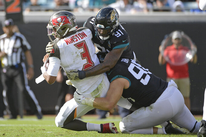 Tampa Bay Buccaneers quarterback Jameis Winston (3) is sacked by Jacksonville Jaguars defensive end Yannick Ngakoue (91) and defensive tackle Taven Bryan, right, during the first half of an NFL football game, Sunday, Dec. 1, 2019, in Jacksonville, Fla. (AP Photo/Phelan M. Ebenhack)