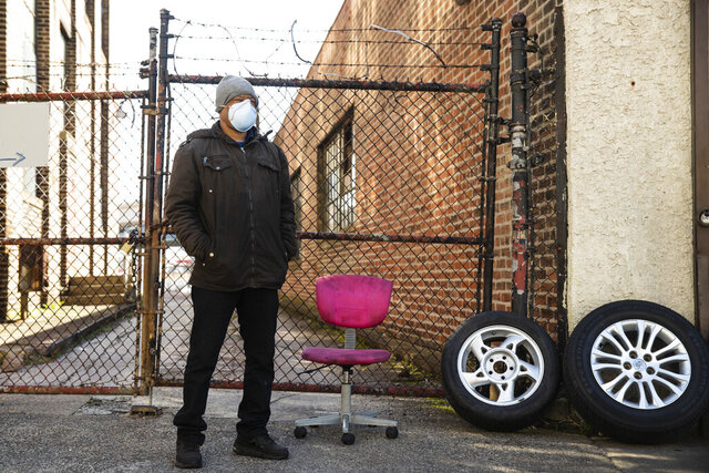 Tire shop owner M. Hernandez, wearing a protective face mask, waits for customers outside his shop in Philadelphia, Thursday, March 26, 2020. Gov. Tom Wolf's administration reported more new coronavirus-related deaths in Pennsylvania on Wednesday. Residents are ordered to stay home, with few exceptions. (AP Photo/Matt Rourke)