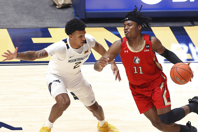 Northeastern guard Jahmyl Telfort (11) is defended by West Virginia forward Jalen Bridges (2) during the second half of an NCAA college basketball game Tuesday, Dec. 29, 2020, in Morgantown, W.Va. (AP Photo/Kathleen Batten)