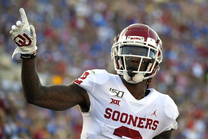 FILE - In this Sept. 14, 2019, file photo, Oklahoma wide receiver CeeDee Lamb celebrates after scoring a touchdown during the first half of an NCAA college football game against UCLA, in Pasadena, Calif. Lamb was selected to the AP Midseason All-America NCAA college football team, Tuesday, Oct. 15, 2019. (AP Photo/Mark J. Terrill)