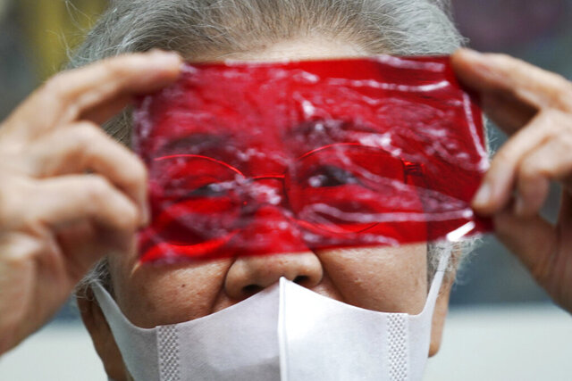 Kisako Motoki, 86, speaks, looking though a red cellophane depicting what she saw the atmosphere of the night of the Great Tokyo Air Raid on March 10, 1945, during an interview with the Associated Press at the Center for the Tokyo Raids and War Damage in Tokyo Wednesday, July 29, 2020.  In Japan, war orphans were punished for surviving. They were bullied. They were called trash, sometimes rounded up by police and put in cages. Some were sent to institutions or sold for labor. They were targets of abuse and discrimination. Now, 75 years after the war's end, some are revealing their untold stories of recovery and pain, underscoring Japan's failure to help its own people. (AP Photo/Eugene Hoshiko)