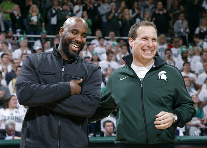 FILE - In this Dec. 12, 2015 file photo, former Michigan State players Mateen Cleaves, left, and Mat Ishbia laugh as they are introduced with Michigan State's 2000 national championship team during halftime of the Michigan State-Florida NCAA college basketball game, in East Lansing, Mich. A suburban Detroit mortgage company led by Ishaba, will pay $500 a month to all basketball and football players at the university. (AP Photo/Al Goldis)