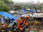 Rescuers perform search operation after a wall collapsed on several slum houses heavy monsoon rains in the Mahul area of Mumbai, India, Sunday, July 18, 2021. More than a dozen people were killed in the incident. (AP Photo/Rajanish Kakade)