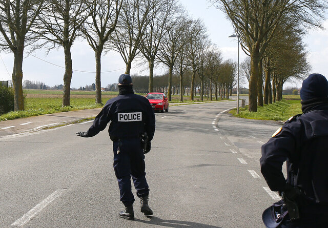 FILE - In this photo taken on March 21, 2020 police officers check on motorists in Baisieux, on the Belgian-French boarder, northern France. Criminals have spotted a new business opportunity with the coronavirus pandemic and are now plundering the needy and the fearful and even disrupting the medical sector, online and off, with fraud, counterfeit products and cybercrime, a report issued Friday by the European law enforcement agency Europol says. The new coronavirus causes mild or moderate symptoms for most people, but for some, especially older adults and people with existing health problems, it can cause more severe illness or death. (AP Photo/Michel Spingler, File)
