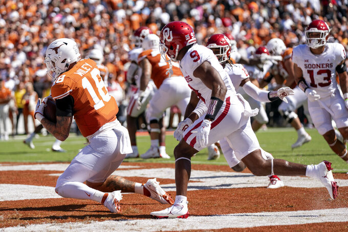 Texas tight end Jared Wiley (18) makes a touchdown catch in front of Oklahoma cornerback D.J. Graham (9) during the first half of an NCAA college football game at the Cotton Bowl, Saturday, Oct. 9, 2021, in Dallas. (AP Photo/Jeffrey McWhorter)