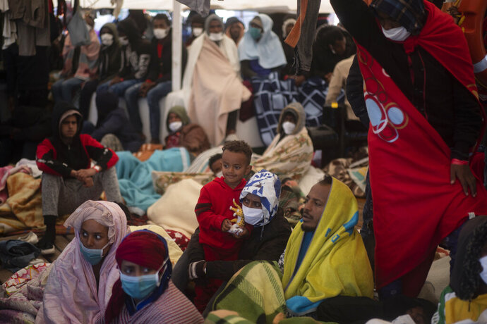 Migrants from Eritrea, Egypt, Syria and Sudan, rest on board the Spanish NGO Open Arms vessel after having been rescued in the Mediterranean sea, about 110 miles north of Libya, on Saturday, Jan. 2, 2021. (AP Photo/Joan Mateu)