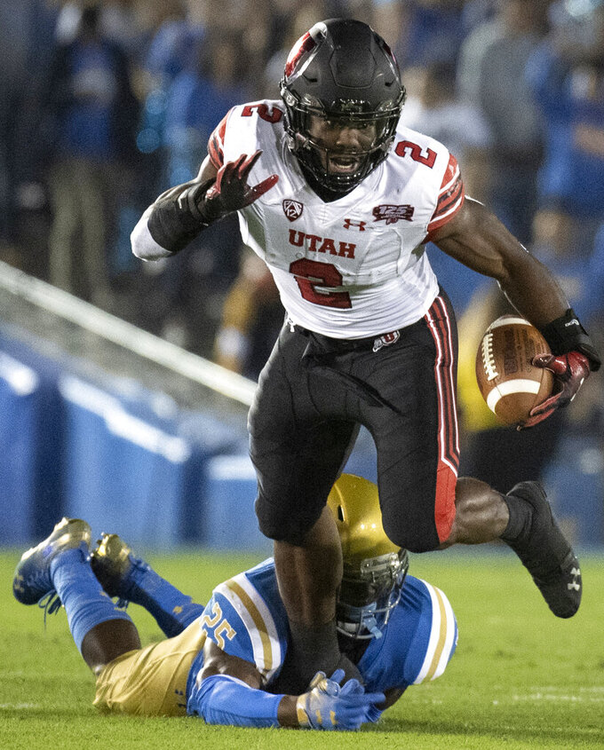 FILE - In this Oct. 26, 2018, file photo, Utah running back Zack Moss, top, sprints over a tackle by UCLA linebacker Tyree Thompson during the first half of an NCAA college football game, in Pasadena, Calif. Moss turned more than a few heads when he chose to return to Utah for his senior season. The decision felt like a simple one for Moss. He wanted to be the first in his family to graduate with a college degree. The 5-foot-10 running back also believed he had some unfinished business on the field. (AP Photo/Kyusung Gong, File)