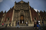 Pedestrians wearing protective face masks as a precaution against the new coronavirus, walk past an entrance to the Metropolitan Cathedral situated on the Zocalo, the main plaza of Mexico City, Thursday, July 2, 2020. The limited reopening of restaurants and other businesses in the capital came as COVID-19 cases continued to climb steadily. (AP Photo/Fernando Llano)