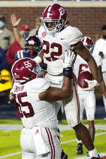 Alabama offensive lineman Emil Ekiyor Jr. (55) lifts running back Najee Harris (22) in celebration after Harris broke a Mississippi tackle and scored a touchdown during the first half of an NCAA college football game in Oxford, Miss., Saturday, Oct. 10, 2020. (AP Photo/Rogelio V. Solis)