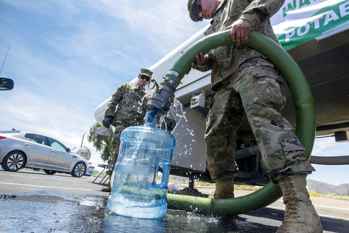 FILE - In this July 9, 2019 file photo, Private First Class Evan Siebuhr, left, and Private First Class Henry Marquez of the 670th Military Police fill water bottles for residents in Trona, Calif., following two strong earthquakes. Residents of this small Southern California desert community hit hard by this month's big earthquakes no longer need to boil tap water. San Bernardino County authorities announced Wednesday, July 18, 2019, the boil-water notice for Trona and neighboring areas has been lifted and citizens do not need to rely on bottled water. (James Quigg/The Daily Press via AP, File)
