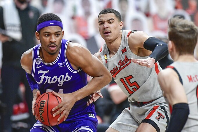 TCU's Kevin Easly Jr. (34) controls the ball against Texas Tech's Kevin McCullar (15) during the first half of an NCAA college basketball game in Lubbock, Texas, Tuesday, March 2, 2021. (AP Photo/Justin Rex)