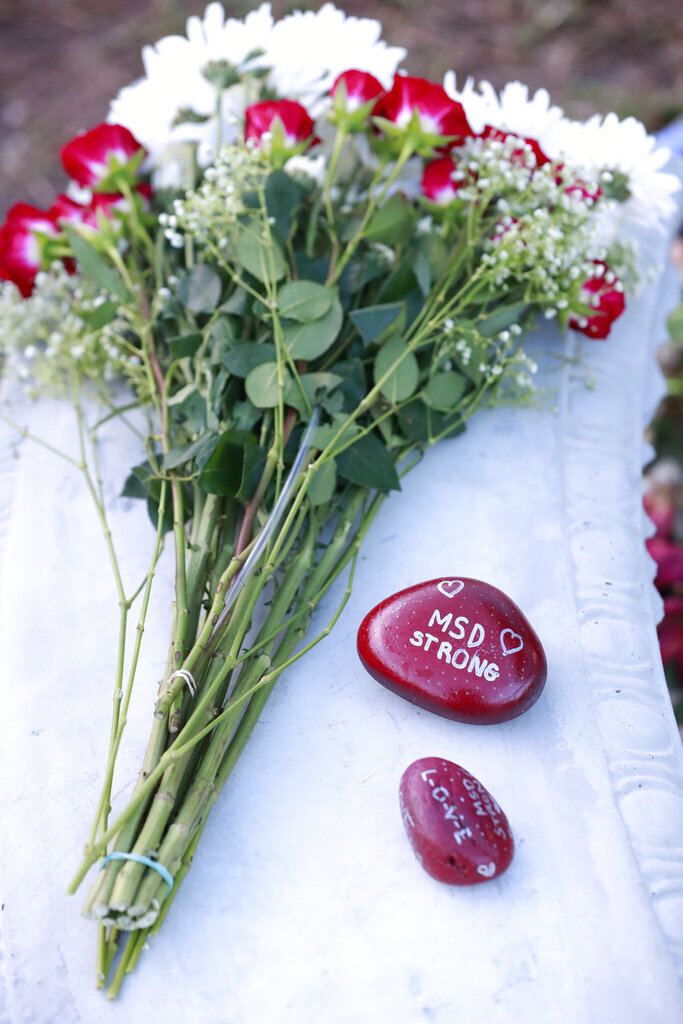 Flowers and stones are shown at a memorial outside Marjory Stoneman Douglas High School during the one-year anniversary of the school shooting, Thursday, Feb. 14, 2019, in Parkland, Fla.  A year ago on Thursday, 14 students and three staff members were killed when a gunman opened fire at the high school.  (AP Photo/Wilfredo Lee)