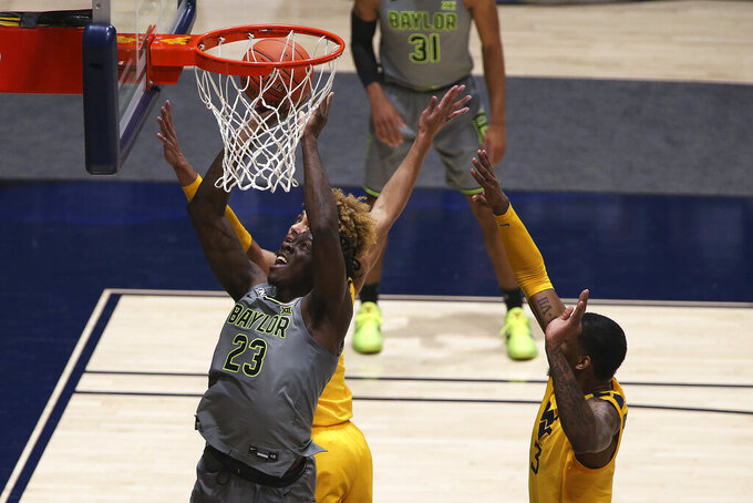 Baylor forward Jonathan Tchamwa Tchatchoua (23) shoots as West Virginia forwards Emmitt Matthews Jr. (11) and Gabe Osabuohien (3) defend during the second half of an NCAA college basketball game Tuesday, March 2, 2021, in Morgantown, W.Va. (AP Photo/Kathleen Batten)