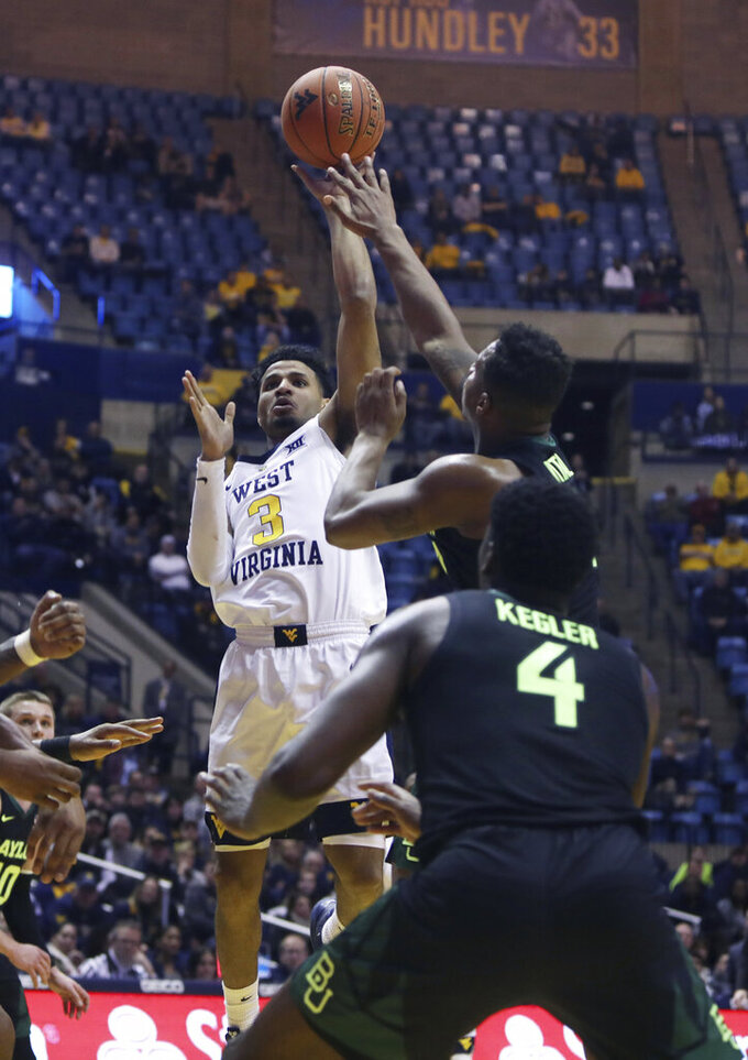 West Virginia guard James Bolden (3) shoots while defended by Baylor guard Mark Vital (11) during the second half of an NCAA college basketball game Monday, Jan. 21, 2019, in Morgantown, W.Va. (AP Photo/Raymond Thompson)