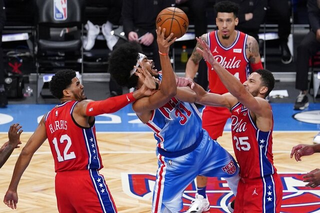 Brooklyn Nets' Jarrett Allen (31) shoots between Philadelphia 76ers' Ben Simmons (25) and Tobias Harris (12) during the second half of an NBA basketball game Thursday, Jan. 7, 2021, in New York. (AP Photo/Frank Franklin II)