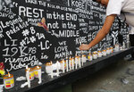 Candles are lit beside a wall full of messages for former NBA basketball player Kobe Bryant at a basketball court in Taguig, south of Manila, Philippines on Tuesday, Jan. 28, 2020. Artists in this tenement building gathered and painted this image after learning of Bryant's death. Bryant, his daughter and 7 others died in a helicopter crash. (AP Photo/Aaron Favila)