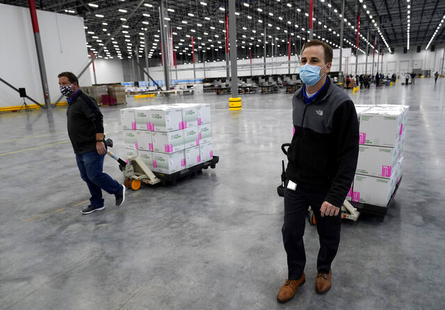 Boxes containing the Moderna COVID-19 vaccine are moved to the loading dock for shipping at the McKesson distribution center in Olive Branch, Miss., Sunday, Dec. 20, 2020. (AP Photo/Paul Sancya, Pool)