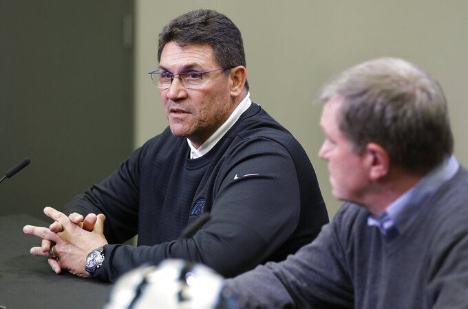 Carolina Panthers head coach Ron Rivera, left, speaks to the media as general manager Marty Hurney listens in Charlotte, N.C., Wednesday, April 17, 2019, in advance of the NFL draft. (AP Photo/Chuck Burton)