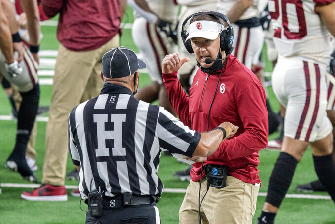 Oklahoma head coach Lincoln Riley talks with head linesman George Gusman during the first half of the the Big 12 Conference championship NCAA college football game against Iowa State, Saturday, Dec. 19, 2020, in Arlington, Texas. (AP Photo/Jeffrey McWhorter)