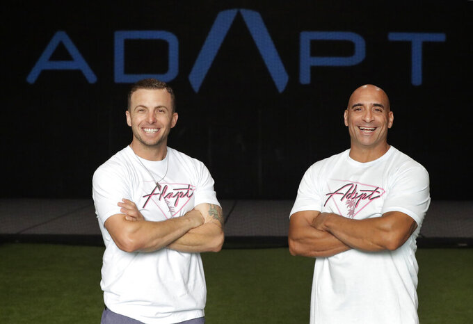 In this Thursday, June 4, 2020 photo, ADAPT gym owners Scott Grondin, left, and Jorge Sanchez pose for a photo at the gym in North Miami, Fla. The business partners and co-founders of the gym just got the OK to reopen their Miami area studio Monday after three months. Desperate to keep their carefully built 15-person team, they gave up their own salaries to keep the entire staff at full pay, relying on them to quickly pivot to online fitness training. (AP Photo/Wilfredo Lee)