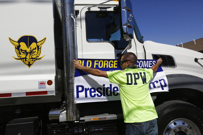 A Trump supporter positions a banner on a Department of Public Works vehicle before the arrival of President Donald Trump, who is scheduled to visit Mariotti Building Products, Thursday, Aug. 20, 2020, in Old Forge, Pa. (AP Photo/Jacqueline Larma)