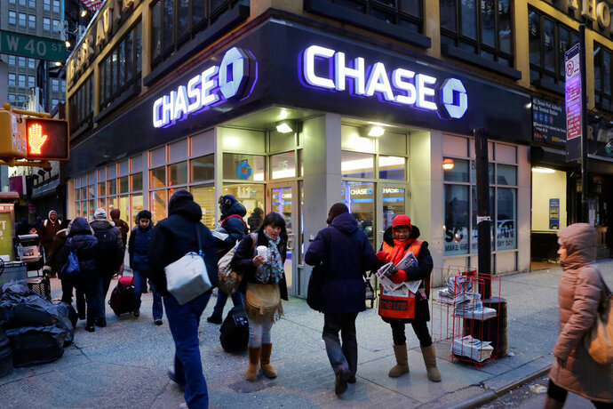 FILE - In this Jan. 14, 2015, file photo, people walk past a branch of Chase bank, in New York. JPMorgan Chase & Co. reports earnings Friday, April 13, 2018. (AP Photo/Mark Lennihan, File)