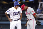 Los Angeles Dodgers' Julio Urias, left, chats with Philadelphia Phillies second baseman Jean Segura after hitting an RBI ground-rule double during the fourth inning of a baseball game Tuesday, June 15, 2021, in Los Angeles. (AP Photo/Mark J. Terrill)