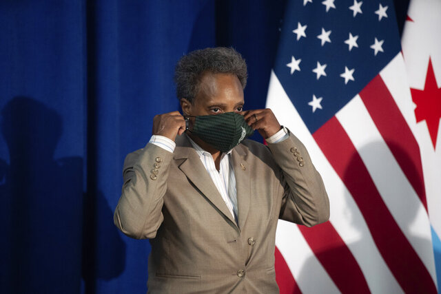 FILE - In this Aug. 5, 2020, file photo, Chicago Mayor Lori Lightfoot wears her mask after speaking about Chicago Public Schools' during a press conference at City Hall in Chicago. Chicago businesses will have to close by 10 p.m. and residents are asked to limit gatherings to six people as the number of newly confirmed coronavirus cases among residents continues to rise. Mayor Lightfoot also announced Thursday, Oct. 22, that bars without food licenses must stop serving customers indoors and liquor sales citywide must end at 9 p.m.  (Pat Nabong/Chicago Sun-Times via AP, File)