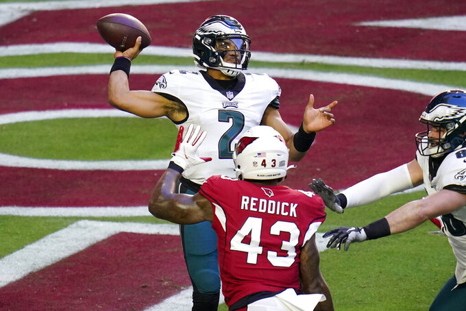 Philadelphia Eagles quarterback Jalen Hurts (2) intentionally grounds the football from the end zone for a safety as Arizona Cardinals outside linebacker Haason Reddick (43) peruses during the first half of an NFL football game, Sunday, Dec. 20, 2020, in Glendale, Ariz. (AP Photo/Ross D. Franklin)