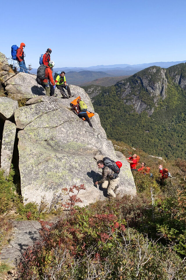 In this photo released by the New Hampshire Fish and Game Department, rescuers hoist the body of a deceased climber on Monday, Sept. 21, 2020, in Franconia Notch State Park in New Hampshire. Benjamin Kessel, 34, of Somerville, Mass., died Sunday, Sept. 20 from a 150-foot fall while climbing on Cannon Cliff after a large boulder dislodged and severed his climbing rope. (Josiah Towne/New Hampshire Fish and Game Department via AP)