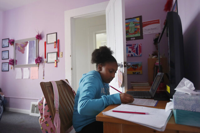FILE - In this April 9, 2020, file photo, Sunnyside Elementary School fourth-grader Miriam Amacker does school work in her room at her family's home in San Francisco. Teachers across the country report their attempts at distance learning induced by the pandemic are failing to reach large numbers of students. (AP Photo/Jeff Chiu, File)