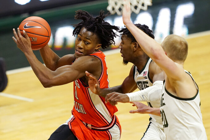 Illinois guard Ayo Dosunmu (11) drives as Michigan State guard A.J. Hoggard, center, and forward Joey Hauser defend during the first half of an NCAA college basketball game, Tuesday, Feb. 23, 2021, in East Lansing, Mich. (AP Photo/Carlos Osorio)