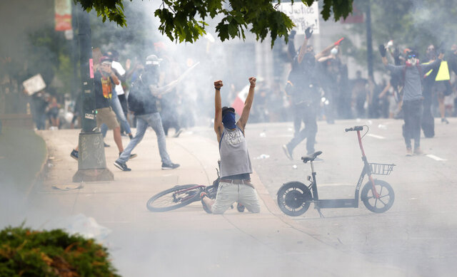 Tear gas fills the air after Denver Police fired canisters during a protest outside the State Capitol over the death of George Floyd, Saturday, May 30, 2020, in Denver. Protests were held in U.S. cities over the death of Floyd, a black man who died after being restrained by Minneapolis police officers on May 25. (AP Photo/David Zalubowski)