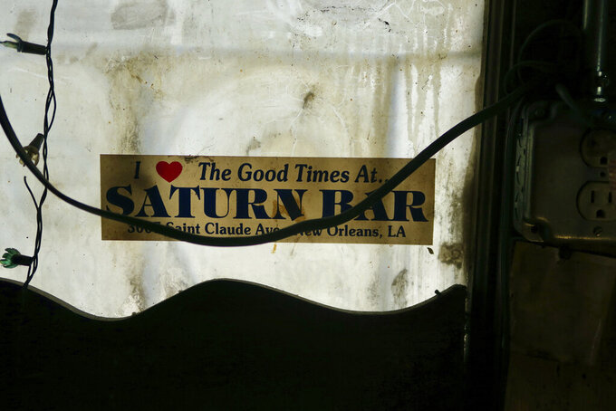 An old bumper sticker in the window of Saturn Bar, which is now preparing to reopen later in 2021. (Ian McNulty/The Times-Picayune/The New Orleans Advocate via AP)