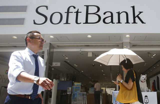 FILE - In this Aug. 7, 2019, file photo, people walk by a SoftBank shop in Tokyo. Japanese technology conglomerate SoftBank Group Corp. saw its April-June profit rise 12% as its investments added to its coffers, including sales of U.S. carrier T-Mobile shares. (AP Photo/Koji Sasahara, File)