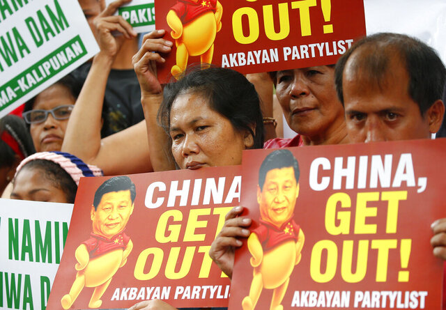 FILE - In this Nov. 21, 2018, file photo, demonstrators rally outside the Chinese Consulate to protest the two-day state visit in the country of President Xi Jinping in Manila, Philippines. The Philippines on Wednesday, April 22, 2020, has protested China's declaration of a Manila-claimed South China Sea area as part of Chinese territory and the aiming of a weapon on a Philippine navy ship, the country's top diplomat said Wednesday. (AP Photo/Bullit Marquez, File)