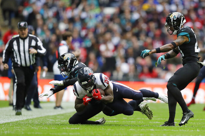 Jacksonville Jaguars defensive back Cody Davis (22) hits Houston Texans running back Duke Johnson (25) during the first half of an NFL football game at Wembley Stadium, Sunday, Nov. 3, 2019, in London. (AP Photo/Kirsty Wigglesworth)