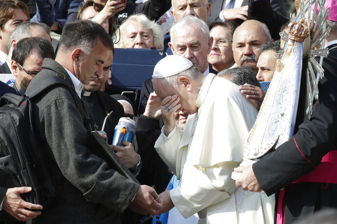 Pope Francis appears to wipe away tears as he stands in front of a plaque honoring war dead in Argentina during a ceremony for the return of a Virgin Mary statue from Britons to Argentina, at the end of his weekly general audience in St. Peter's Square, at the Vatican, Wednesday, Oct. 30, 2019. The original statue of the Virgin Mary, Patroness of Argentina, which was brought to Britain at the end of the Falklands War, will be returned to Argentina and its replica, made in Argentina, will be donated to the Catholic Military Cathedral of St. Michael and St. George in Aldershot, Britain. (AP Photo/Andrew Medichini)