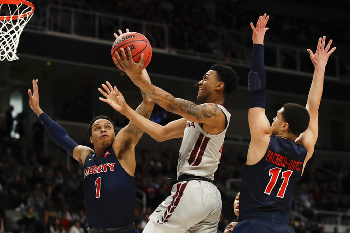Virginia Tech guard Nickeil Alexander-Walker, middle, drives to the basket between Liberty guard Caleb Homesley. Let, and guard Georgie Pacheco-Ortiz during the first half of a second-round game in the NCAA men's college basketball tournament Sunday, March 24, 2019, in San Jose, Calif. (AP Photo/Ben Margot)