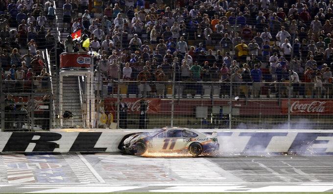 Denny Hamlin (11) crosses the finish line as flames leap from his car during the NASCAR Cup Series auto race at Charlotte Motor Speedway in Concord, N.C., Sunday, May 26, 2019. (AP Photo/Chuck Burton)