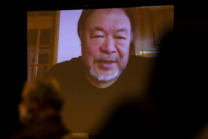 """Chinese artist and  political activist Ai Weiwei, speaking from Lisbon, Portugal, is seen on a screen during a virtual news conference at the Foreign Corespondents' Club of Japan in Tokyo Friday, Jan. 22, 2021. Ai said that his latest documentary """"Coronation"""" has been refused to be exhibited at major film festivals and online TV platforms due to its sensitivity. (AP Photo/Hiro Komae)"""