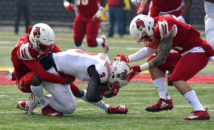 North Carolina State wide receiver Kelvin Harmon (3) is brought down by Louisville cornerback Anthony Johnson, left and safety London Iakopo (21) during the first half of an NCAA college football game, in Louisville, Ky., Saturday, Nov. 17, 2018. (AP Photo/Timothy D. Easley)