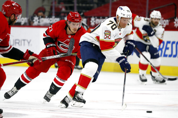 Florida Panthers' Patric Hornqvist (70) skates with the puck after taking it away from Carolina Hurricanes' Brock McGinn (23) during the first period of an NHL hockey game in Raleigh, N.C., Sunday, March 7, 2021. (AP Photo/Karl B DeBlaker)